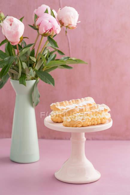 Эклеры на торт стол и пион цветы в вазе — стоковое фото