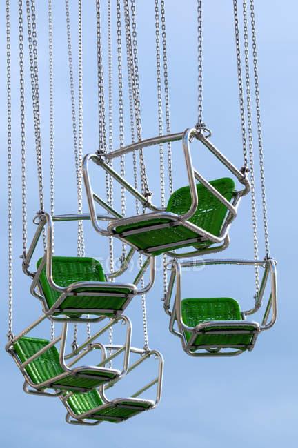 Chaîne de parc d'attractions balançoires, sièges verts contre le ciel bleu — Photo de stock