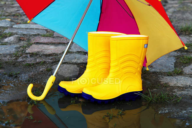 Cold autumn weather, colorful umbrella and yellow galoshes — Stock Photo