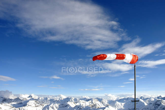 Wind vane on top of snow covered mountains — Stock Photo