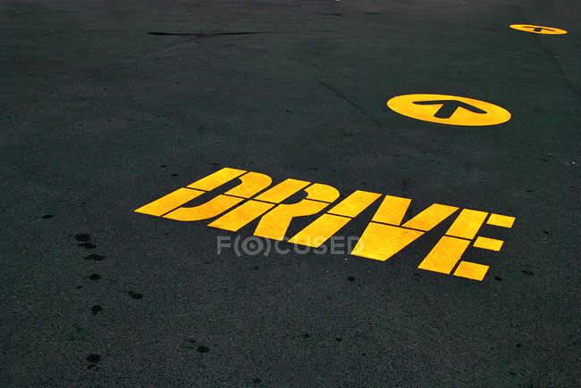 Асфальтовая дорога с желтый диск Руководство и стрелка — стоковое фото