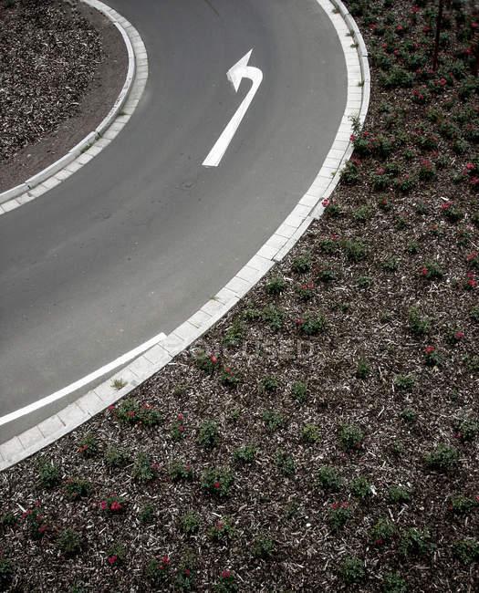 Strada curva con vista freccia l'asfalto, girare a sinistra — Foto stock