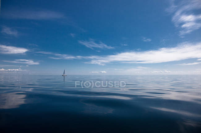 Sailboat floating in blue sea water on horizon — стокове фото