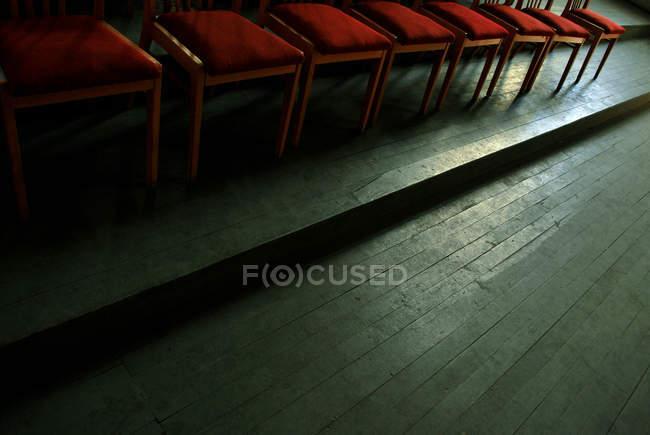 Деревянный пол и красные стулья — стоковое фото