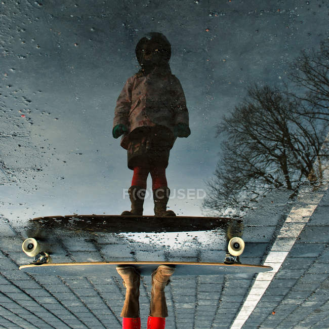 Reflection of child standing with skateboard in puddle — Stock Photo