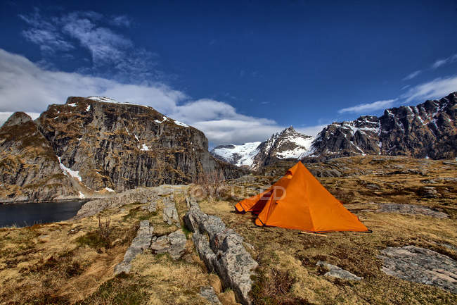Adventure orange camping tent in rocky mountains — Stock Photo