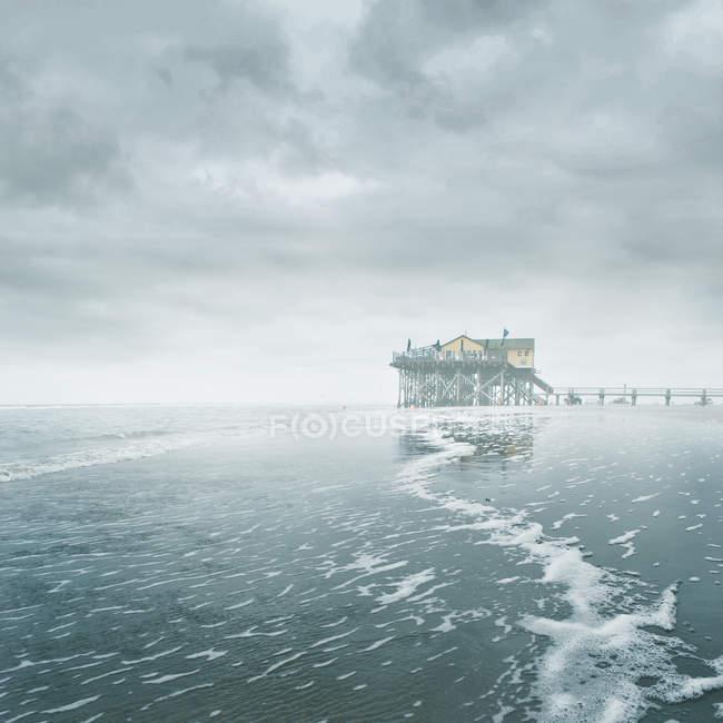 Схожого на ходулі будинок на замерзле море зимових — стокове фото