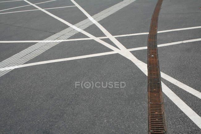 Strada asfaltata con linee bianche dipinte e sistema di drenaggio — Foto stock