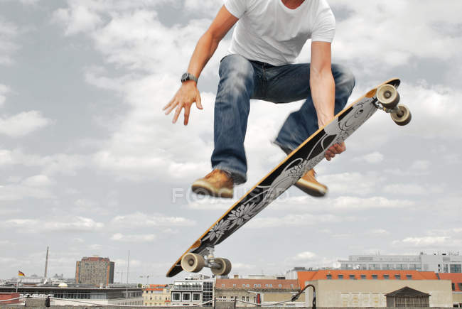 Skater jumping with longboar, city buildings on background — Stock Photo