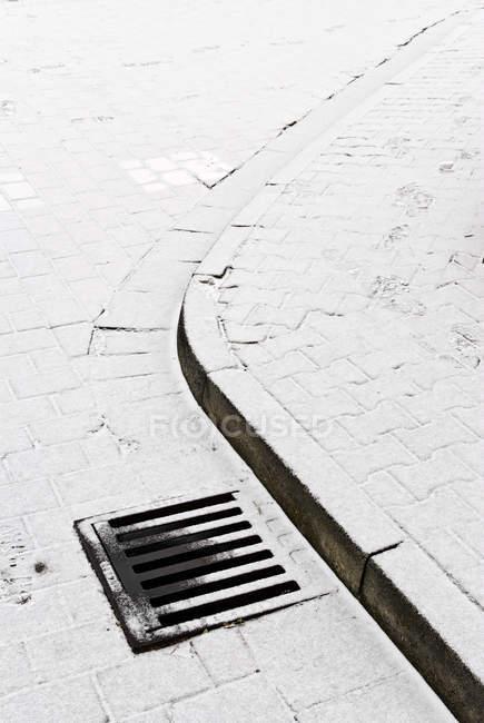Estrada de rua nevada com tampa de bueiro no passeio — Fotografia de Stock