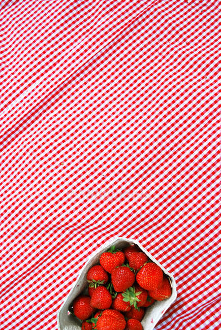 Strawberry bowl on table cloth — Stock Photo