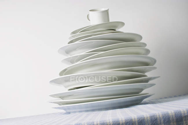 Dishware plates stack on table with cup — Stock Photo
