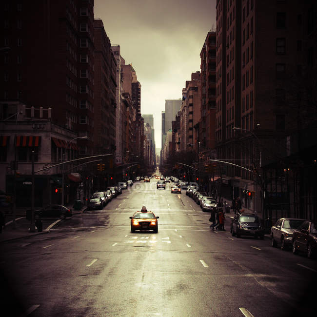 New York city architecture and road with cars and walking people — Stock Photo