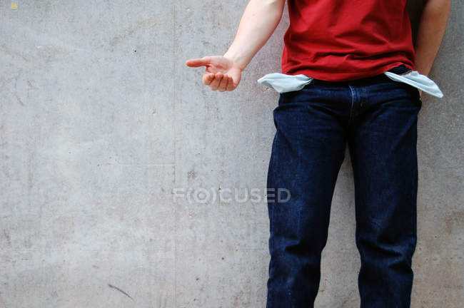 Imagem cortada de pessoa implorando com a mão enquanto em pé na parede cinza de concreto — Fotografia de Stock