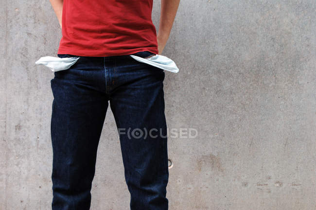 Cropped image of poor person standing at wall with hands behind back, pockets out — Stock Photo
