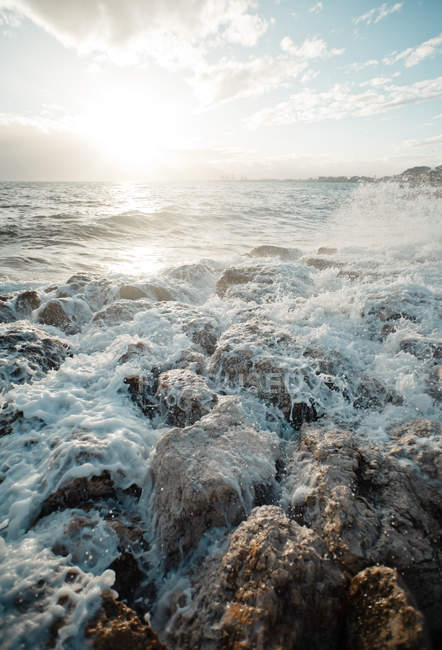 Sea water with splashes and rocks at shore — Stock Photo