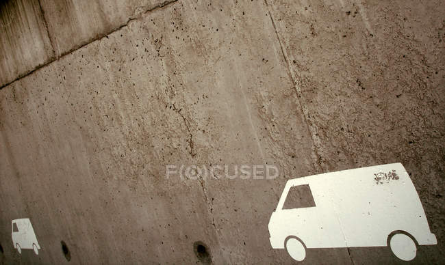 Brown concrete wall with painted white cars — Stock Photo