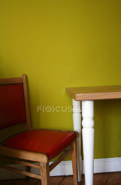 Cadeira vermelha e mesa de madeira na sala com parede verde — Fotografia de Stock