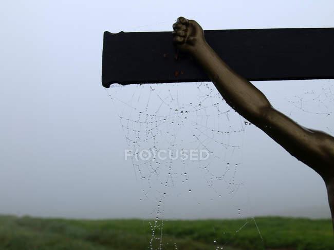 Spinnennetz auf Holz Kreuz mit Jesus Kruzifix hand — Stockfoto