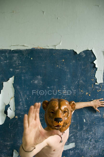 Man wearing bear mask on face and attack while standing at old aged wall in room — Stock Photo