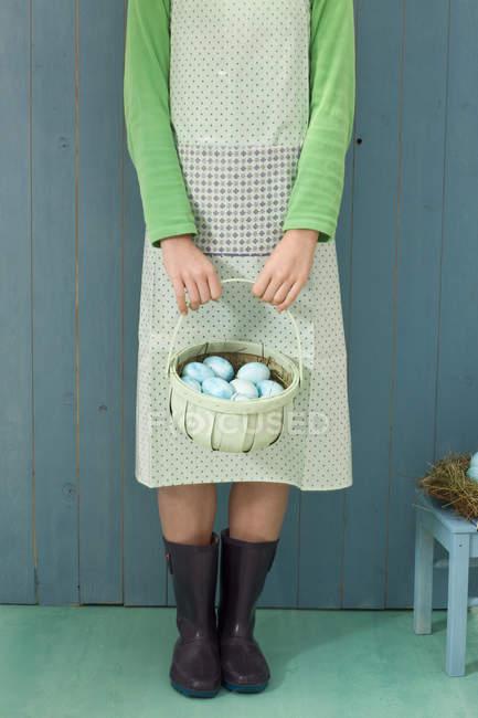 Vista parcial de mulher segurando cesta com ovos de Páscoa — Fotografia de Stock