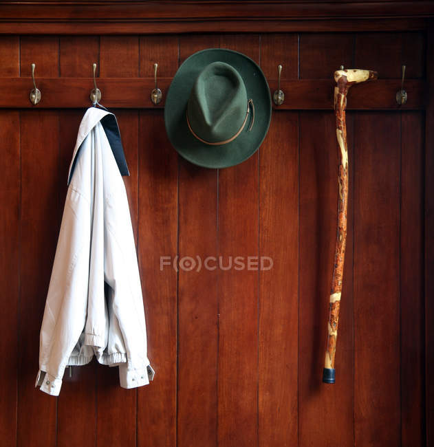 Wooden closet with hangers, hanging jacket, hat and stick — Stock Photo