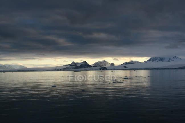 Nuvens de tempestades na Antártida, montanhas coberta de neve e a superfície do mar — Fotografia de Stock