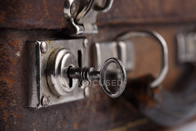 Old brown leather suitcase with key — Stock Photo