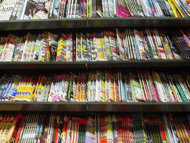 Many publication magazines on wooden shelves in store — Stock Photo