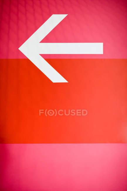 Красная стена с направлением, стрелка слева — стоковое фото