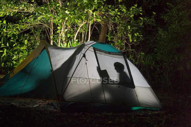 Tente avec des personnes à l'intérieur, nuit camping en forêt — Photo de stock