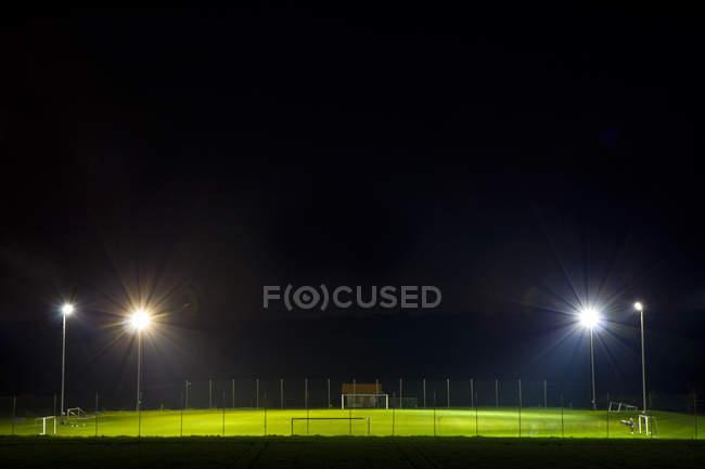 Campo de fútbol con lámparas focos iluminados en la noche - foto de stock