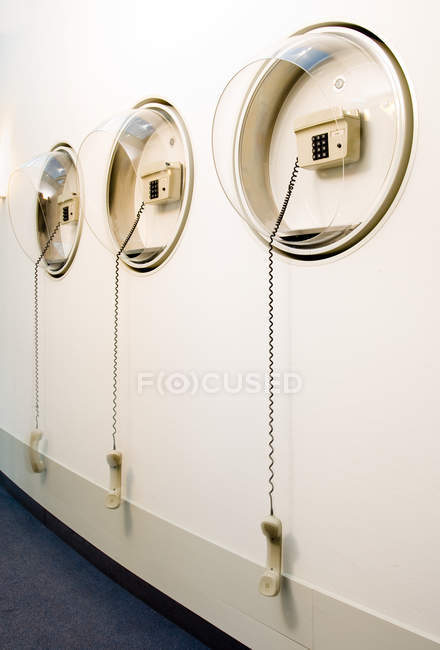 Old fashioned telephones hanging on wall in room — Stock Photo