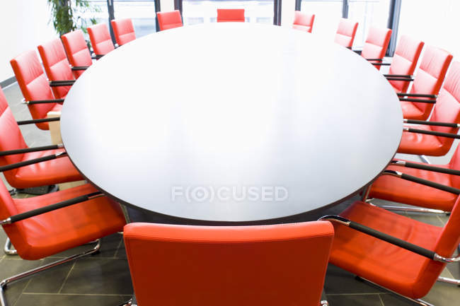 Conference table with red chairs, meeting room — Stock Photo