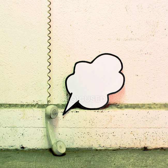 Old telephone hanging on cable at wall with speech bubble — Stock Photo