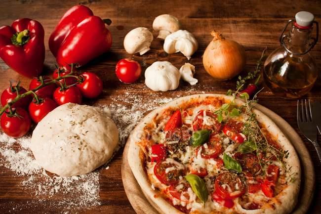Запеченная пиццы и тесто для пиццы с овощами на деревенском стиле таблицы — стоковое фото