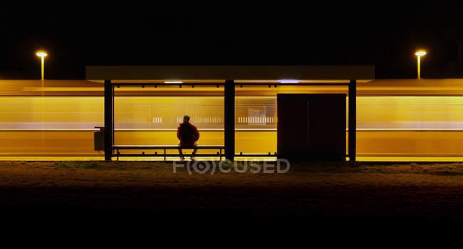 Tiro de noite do homem sentado na paragem de autocarro e esperando — Fotografia de Stock
