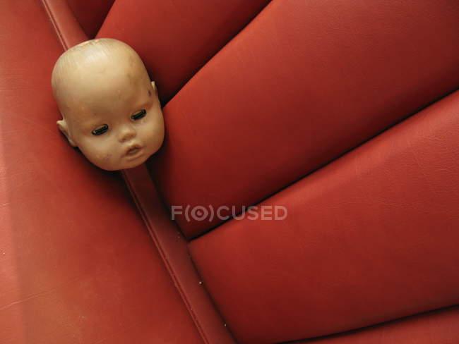Tête de poupée chauve Spooky sur canapé en cuir rouge — Photo de stock