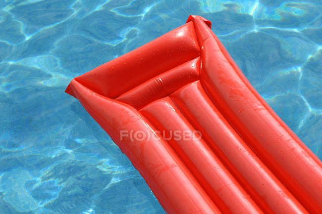 Swimming pool blue water and red raft — Stock Photo