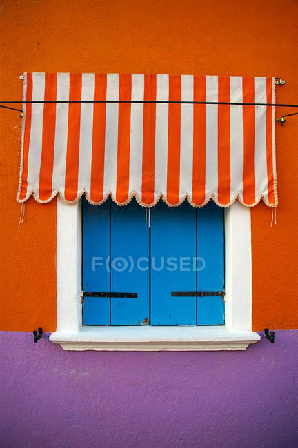 Colorful building house wall with closed blue window shutters — Stock Photo