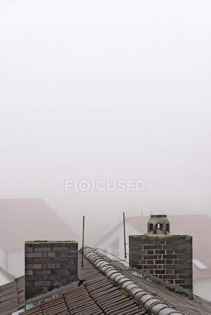 Tetti di casa nella nebbia, autunno mattina presto — Foto stock