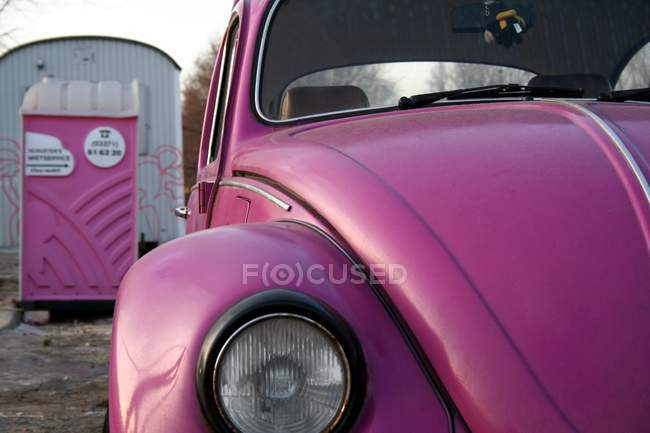 Toilet cabin and purple violet old car headlamp — Stock Photo