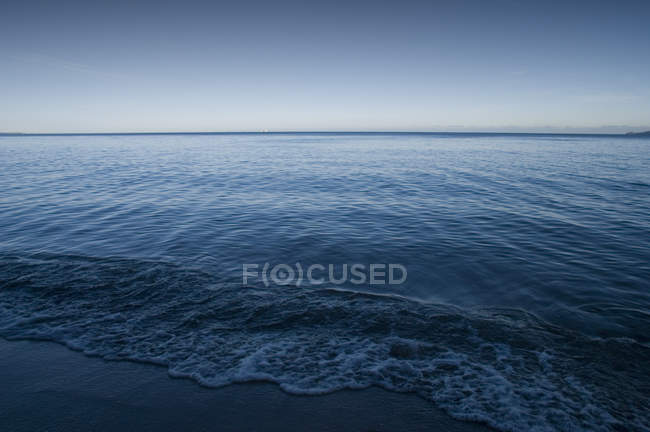Blue sea water surface and clear sky — стокове фото
