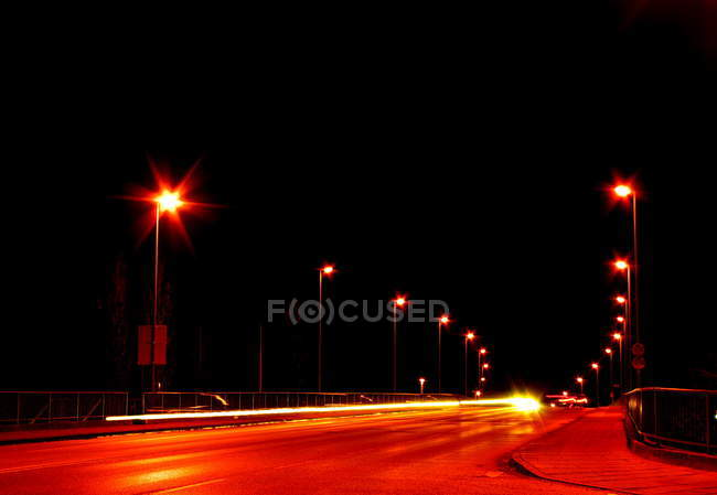 Illuminated road at night, blurred motions of transport and traffic — Stock Photo
