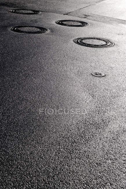 Route asphaltée avec couvercles — Photo de stock