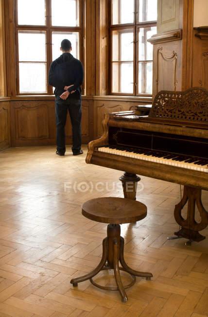 Vista posteriore del pianista musicista in piedi uomo alla finestra in camera con vecchio pianoforte in legno — Foto stock
