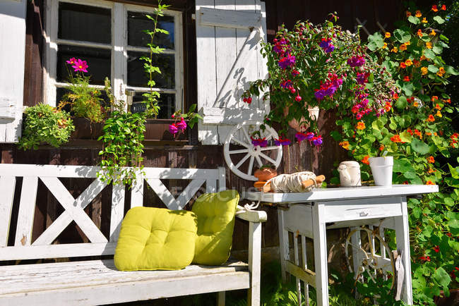 Garden house with bench and flowers pots — Stock Photo