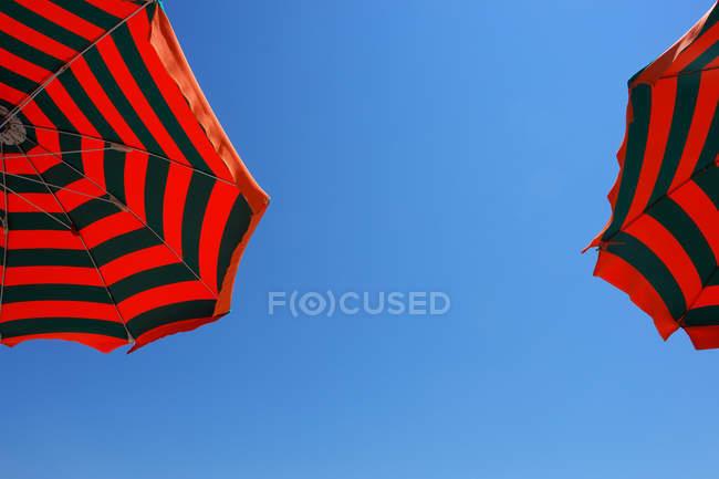 Striped red black umbrellas and blue sky — Stock Photo