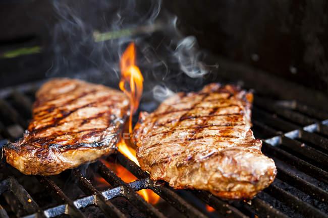 Приготовление стейка мясо на решетке гриль с пламенем — стоковое фото