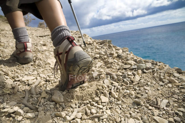 Mountaineering hiking and climbing on rocky hill, cropped image of legs — Stock Photo
